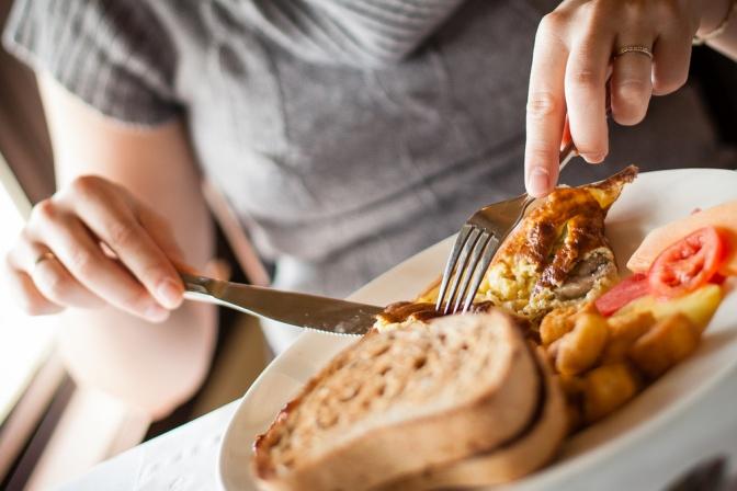Eine Frau sitzt bei einem Teller mit ausgewogenem Essen