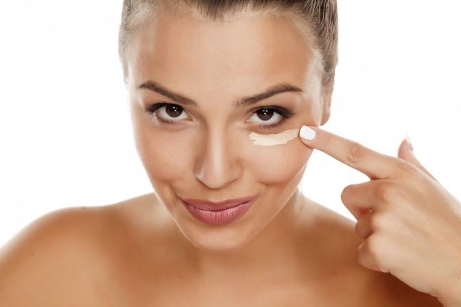 Eine Frau trägt einen Concealer unterm Auge auf