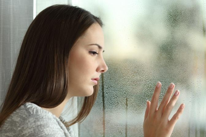 Traurige Frau an einer Fensterscheibe