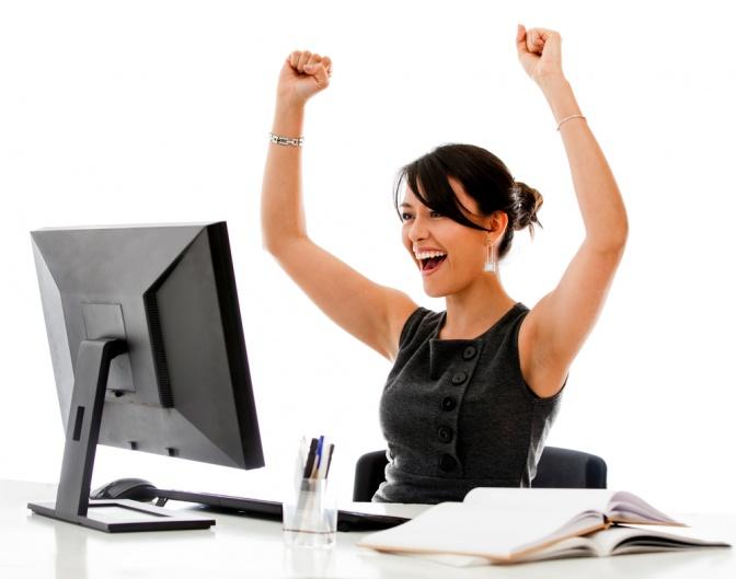 Eine Frau sitzt vor Überengagement als Burnout Phase 1 vor ihrem Computer und freut sich über ihre Arbeit.