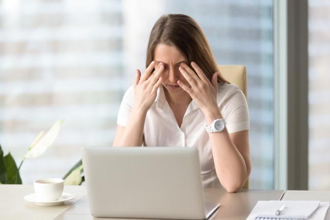 Eine Frau vor dem Laptop reibt ihre Augen