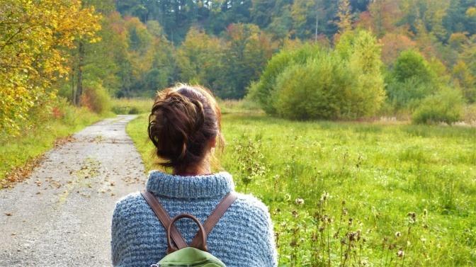 Eine Frau steht in einer sonnenbeschienenen Landschaft