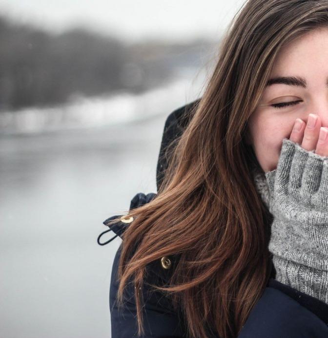 Eine Frau mit glatten Haaren trägt fingerlose Handschuhe und eine dicke Jacke