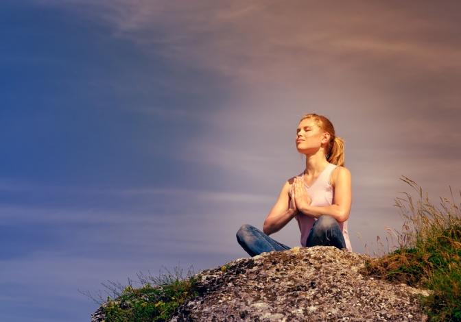Eine Frau sitzt auf einem Stein und übt Yoga aus.