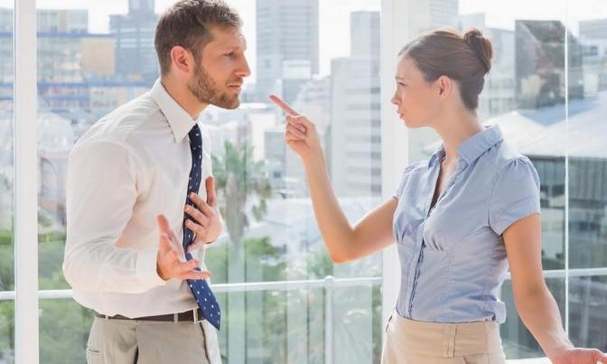 Eine Frau zeigt mit dem Finger auf einen Mann