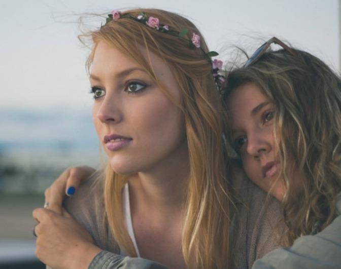 Zwei Frauen umarmen sich und blicken bewusst drein