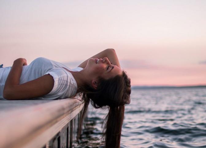 Ein freier Mensch liegt mit dem Rücken auf einem Steg beim Wasser