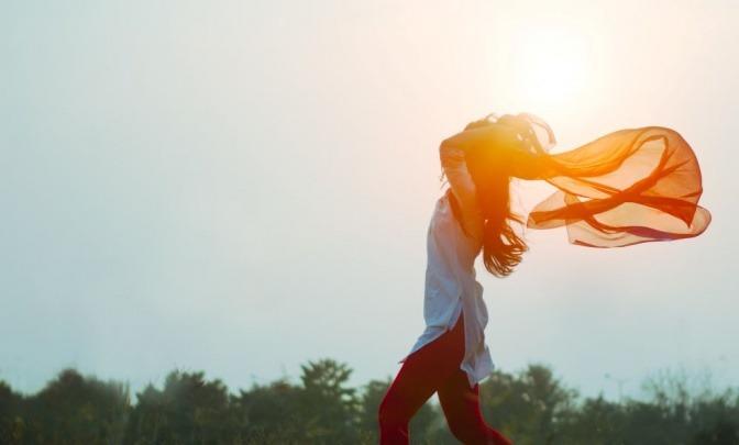 Eine Frau fühlt sich frei und lässt ein Tuch zwischen ihren Armen wehen