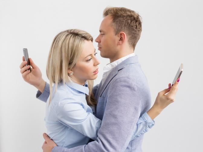 Ein Paar befindet sich in einer Art Umarmung, beide lesen jedoch hinter dem Rücken ihres Partners auf ihren Mobiltelefonen.