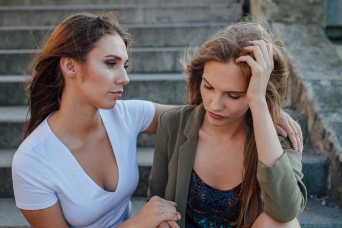 Zwei junge Frauen sitzen auf einer Treppe. Die eine muntert ihre Freundin auf.