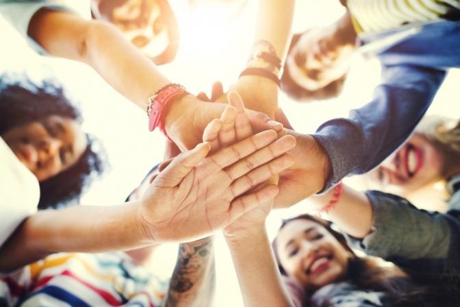 Mehrere befreundete junge Menschen legen ihre Hände übereinander und symbolisieren Geschlossenheit.