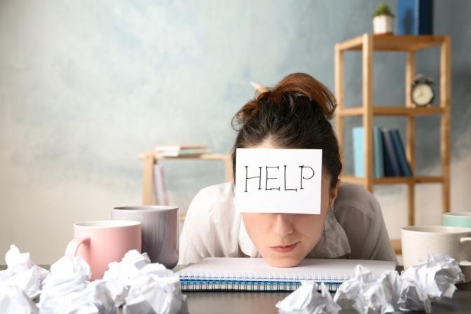 """Eine junge Frau mit einem """"Hilfe""""-Schild auf der Stirn sitzt zusammengekauert am Schreibtisch."""