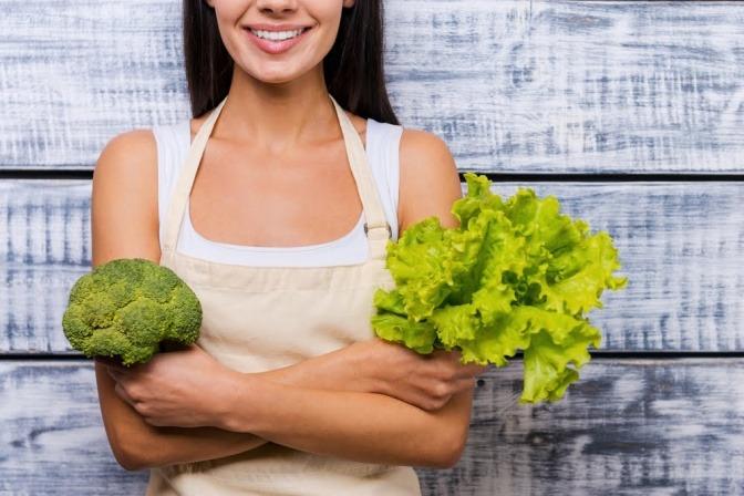 Frau mit grünem Gemüse in der Hand.