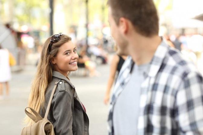 Ein Mann und eine Frau begegnen sich auf der Straße und nehmen Kontakt zueinander auf.