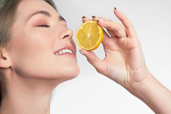 Frau hält eine Zitrone mit Fruchtsäure in der Hand
