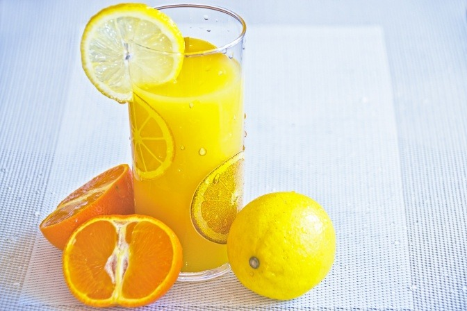 In einem Glas ist Fruchtsaft, daneben liegen Zitrusfrüchte