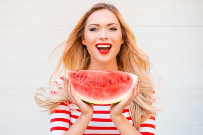 Eine Frau hält eine Wassermelone als Frucht zum Abnehmen