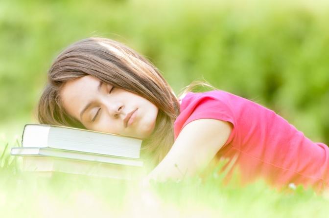 Eine Frau liegt müde im Frühjahr in der Wiese