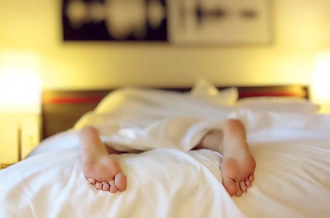 Aus dem Bett ragen nur zwei Füße unter der Decke hervor