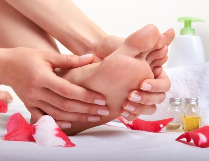 Eine Frau massiert ihren Fuß