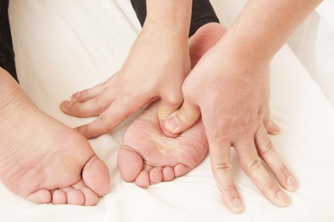 Mit den Finger wird Druck auf bestimmte Fußreflexzonen ausgeübt