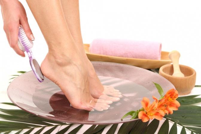 Eine Frau nimmt ein Fußbad gegen Hornhaut