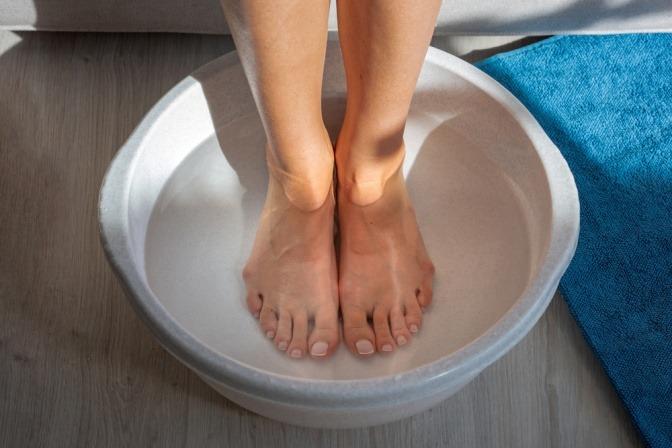 Eine Frau nimmt ein Fußbad gegen riechende Füße