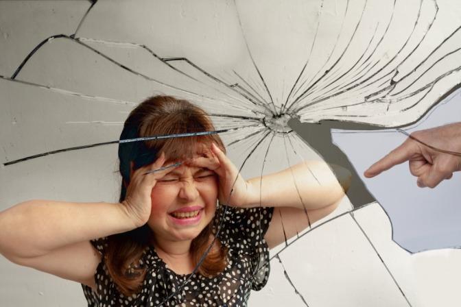 Eine gestresste und verzweifelte Frau steht vor einem zerbrochenen Spiegelbild von sich selbst, während ein Finger auf sie zeigt.