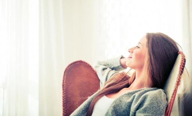 Eine Frau sitzt in einem Ohrensessel und blickt an einem sonnigen Tag durch ein großes Fenster nach draußen. Sie wirkt zufrieden und entspannt.