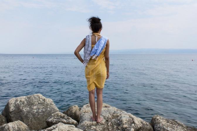 Frau mit einem gebundenen Tuch am Meer auf einem Felsen