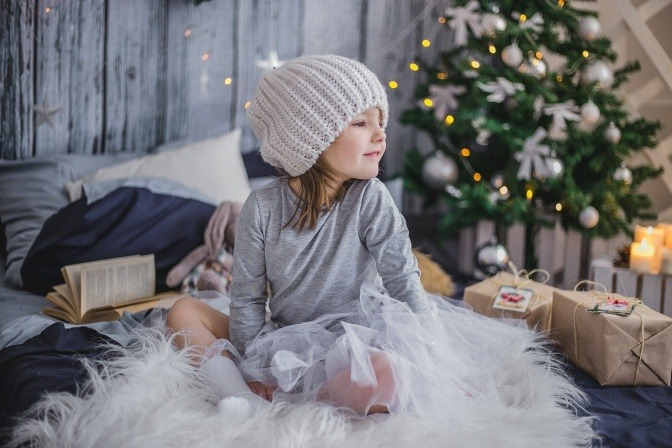 Ein Kind sitzt geduldig neben verpackten Geschenken