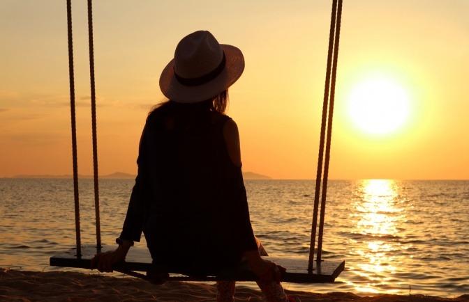 Frau alleine auf Schaukel bei Sonnenuntergang