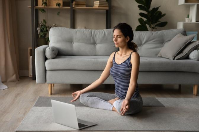 Eine Frau vor dem Laptop bei geführter Meditation gegen Migräne