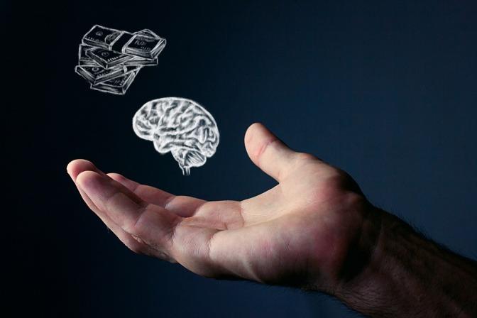 Über einer Hand schweben ein Gehirn und Geld
