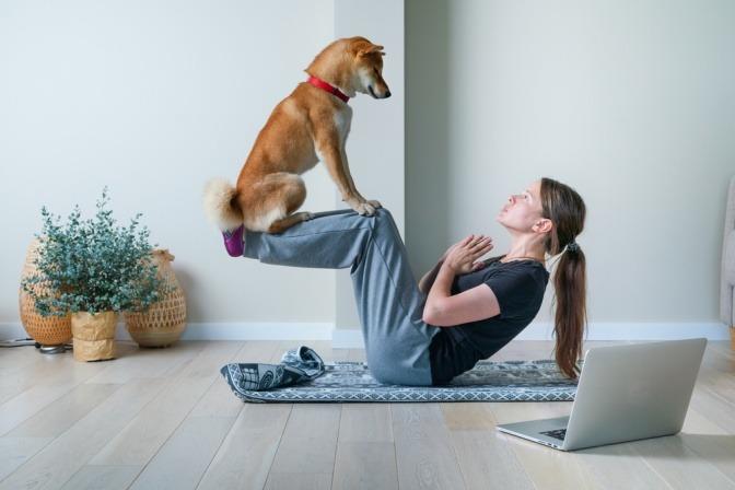 Frau macht Yoga und balanciert dabei einen Hund auf ihren Beinen.