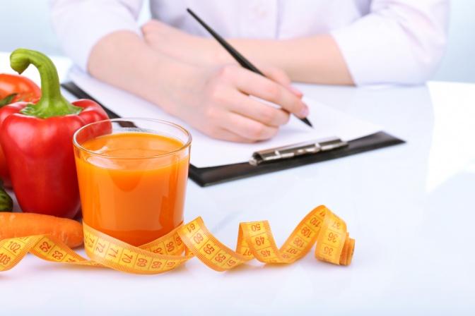 Eine Frau schreibt einen Ernährungsplan, im Vordergrund Gemüsesaft, Gemüse und Maßband
