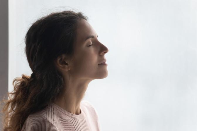 Eine Frau schließt ihre Augen und genießt in sich ruhend den Moment
