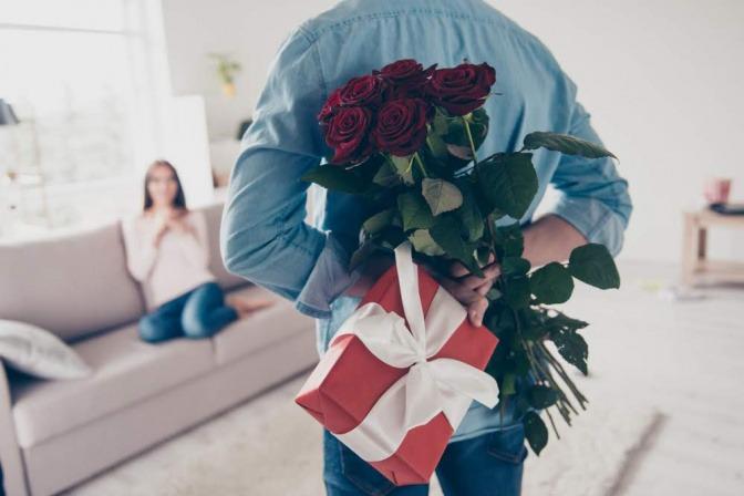 Ein Mann versteckt hinter seinem Rücken Rosen und ein Geschenk