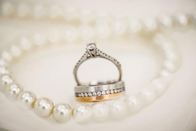 Schmuck (Kette, Ring aus Gold und Silber) liegt auf einer Fläche
