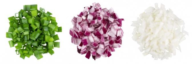Drei kleine Haufen mit geschnittenen Frühlingszwiebeln, weißen Zwiebeln und roten Zwiebeln.