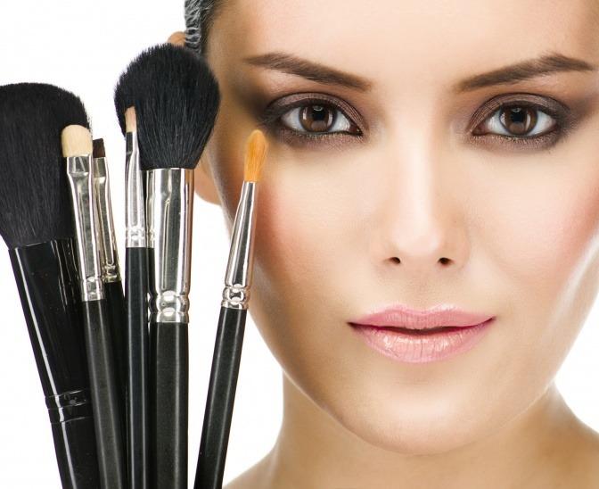 Neben einem Gesicht sind verschiedene Make-up Pinsel