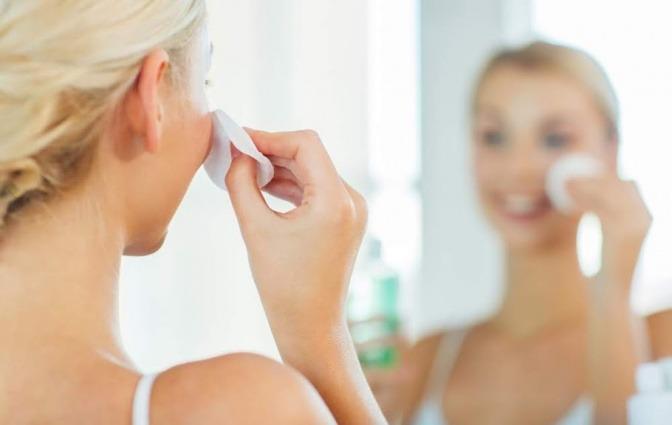 Eine Frau reinigt ihr Gesicht mit einem Wattepad