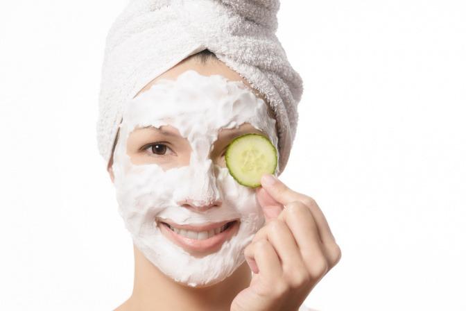 Eine Frau mit einer Scheibe Gurke und einer Gesichtsmaske