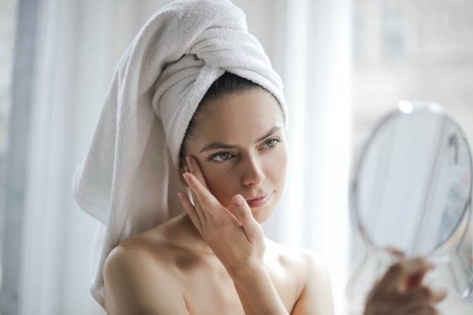 Eine Frau pflegt ihr Gesicht und betrachtet es im Spiegel