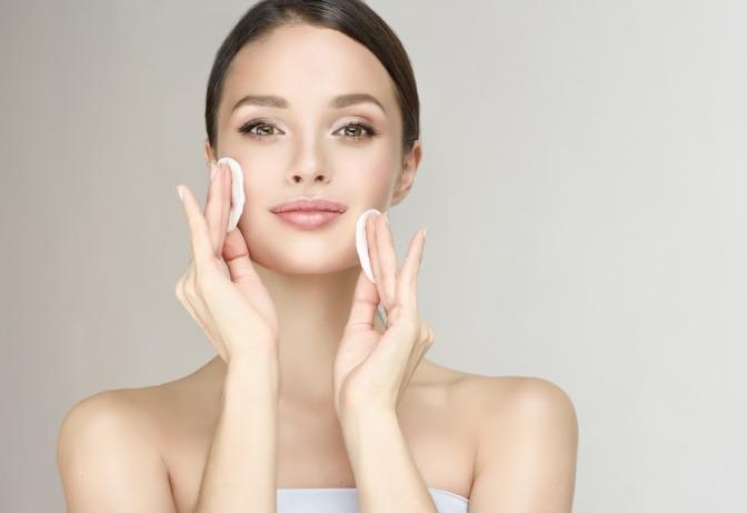 Frau cremt ihr Gesicht mit Naturkosmetik ein