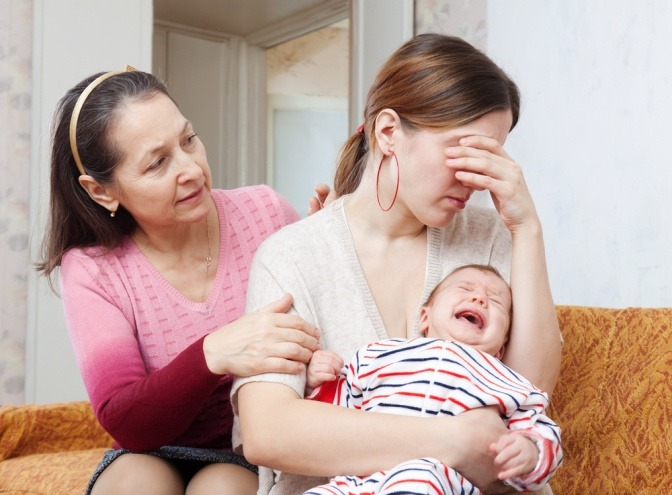 Eine Frau will mit einer weinenden Frau mit Baby sprechen