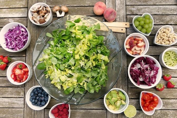 Die Aufnahme aus der Vogelperspektive zeigt einen, mit allerhand gesunden Lebensmitteln, reichhaltig gedeckten Tisch.