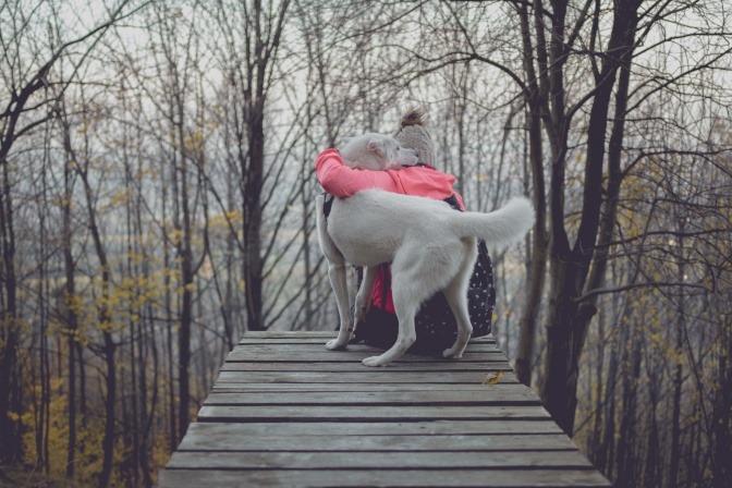 Eine Frau sitzt im Winter an einem Steg und umarmt ihren Hund, der neben ihr sitzt.