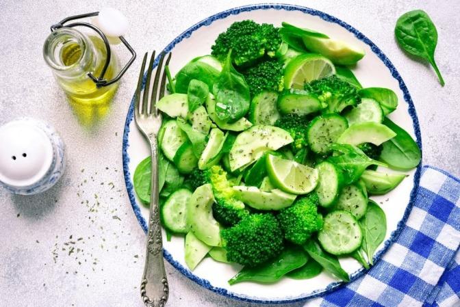 Ein Teller mit einem Gericht, das aus lauter grünem Gemüse wie Broccoli, Rucola und ähnlichem besteht.