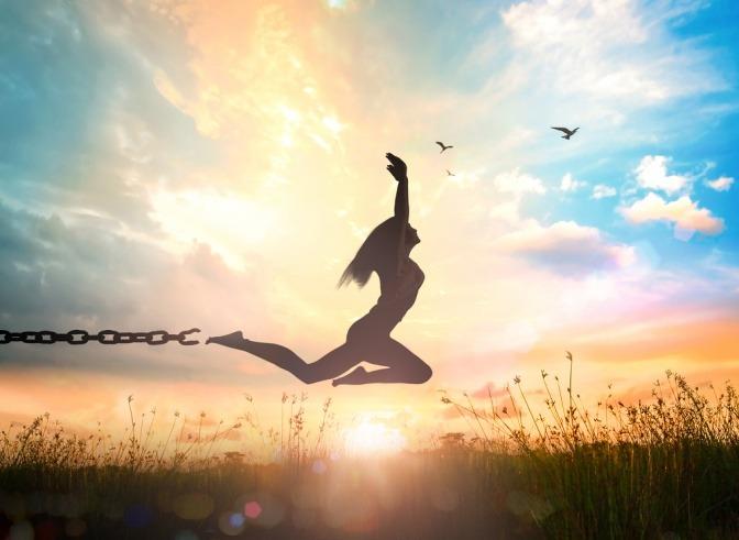 Vor einer untergehenden Sonne springt eine Frau in die Luft und reißt sich dabei von einer Stahlkette los.